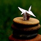 Paper crane on pebbles by retroboho