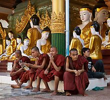 faithful Buddhist monks siiting around Buddha Statues in SHWEDAGON PAGODA by travel4pictures