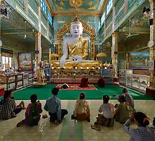faithful Buddhists praying at sitting Buddha in golden Ponnya Shin Pagoda by travel4pictures