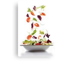 Salad with fresh vegetables falling on plate Canvas Print