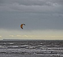 A Lone Kite Surfer Flying Across Stormy Seas by lynn carter