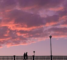 Two people walking on a bridge, in the evening by Olivier Sohn