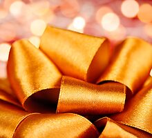 Gold gift bow with festive lights by Elena Elisseeva