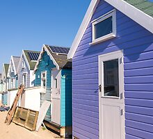 Cluster of pretty pastel beach huts by Zoe Power