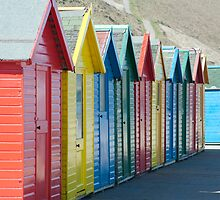 Colourful wooden beach huts by photoeverywhere