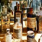 Medicine Bottles in Glass Case by Susan Savad