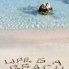 Life is a beach message written on white sand, with tropical sea waves in background by Stanciuc