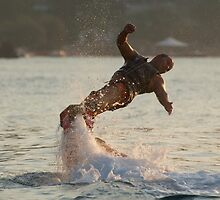 Flyboarder with arms out twisting towards water by Nick Dale
