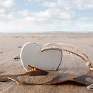 wooden love heart in the sand by morrbyte