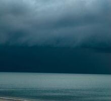Dark storm clouds over a turquoise sea by Rekha Garton