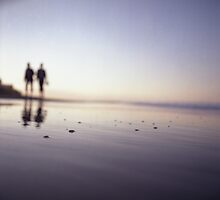 Two people walking on beach on summer evening Hasselblad medium format film analog photograph by edwardolive
