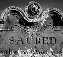Closeup on Tomb stone with inscription Sacred In the Memory Of by Stanciuc