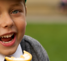 Close-up of laughing uniformed schoolboy eating ice-cream Sticker