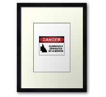 DANGER: CURRENTLY OPERATED BY A MORON Framed Print