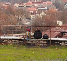 Girl and boy sitting on the edge of the roof of the house. by miniailov