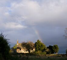 Rainbow shines through dark skies by Mark Baldwyn
