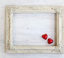 white Wooden frame with red hear shaped chocolates  by PhotoStock-Isra