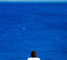Woman looks out at an endless expanse of calm ocean by PhotoStock-Isra