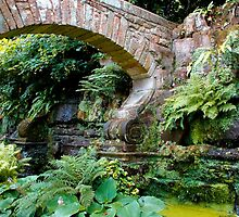 A stone arch decorates the garden by jwwallace