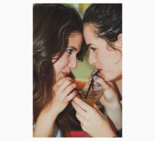 Two young woman share a cocktail  by PhotoStock-Isra