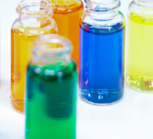 Glass bottles with coloured liquid at a Cosmetics manufacturer Sticker