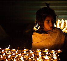Young Nepali girl in candle light by Phil Gribbon