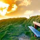 bench on a cliff edge with sunset by morrbyte