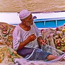 fisherman fixes his net by Amir Sorial