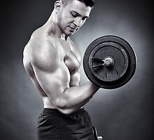 Athletic man working out with heavy dumbbells by naturalis