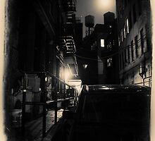 Dark alley with water tower in New York City at night by Reinvention