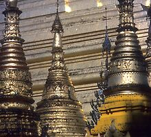 Golden spires of Buddhist stupas in temple by cascoly