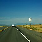 Single car on lonely highway by cascoly