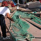 Fisherman with green nylon fishing nets by cascoly