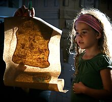 Little girl studying a treasure map by RonnieGinnever