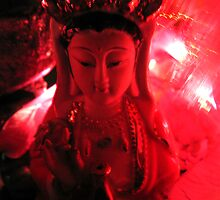 Red Quan Yin backlit with lights made of flower shapes. by Marilyn Baldey
