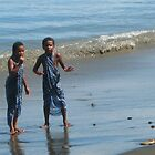 Young girls playing in the surf in Fiji by evon