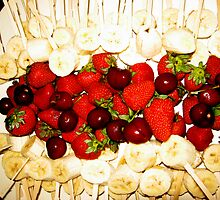 Bananas on a stick , strawberriesand cherries ready to dip in chocolate. by Marilyn Baldey