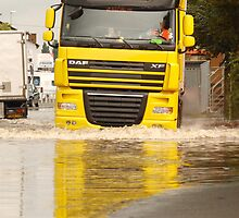 Large DAF articulated lorry driving through summer flash flooding road condition in Britain 2007 by RedSteve