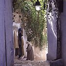 Hooded shopkeeper in alley by heatherf
