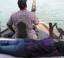 Lady sleeping while boatman steers by ashishagarwal74