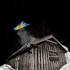 Snowboarder jumping over an old house by Vegard Giskehaug