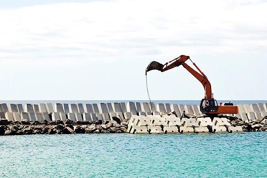 Heavy excavator machine in a pier construction site by mrfotos