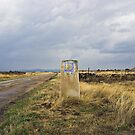 old pilgrim&#x27;s trail marker beneath stormy clouds by Christopher Barton