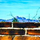 Brick Wall and Mountain Range Landscape by John Corney