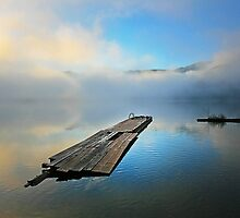 lakescape with low misty clouds reflected on blue by alex skelly