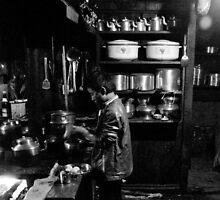 Boy making dinner in moody kitchen by Erdj