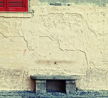 Stone bench, closed shutters and graffiti by Silvia Ganora