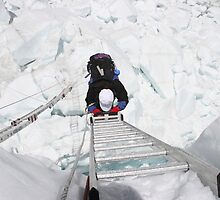 Mt. Everest Climbing crossing ladder through Khumbu icefall.   by climber