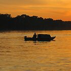 Fisherman at sunset on Danube river by robertpatrick