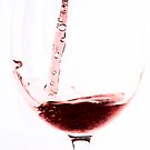 Red wine into wine glass by Arve Bettum